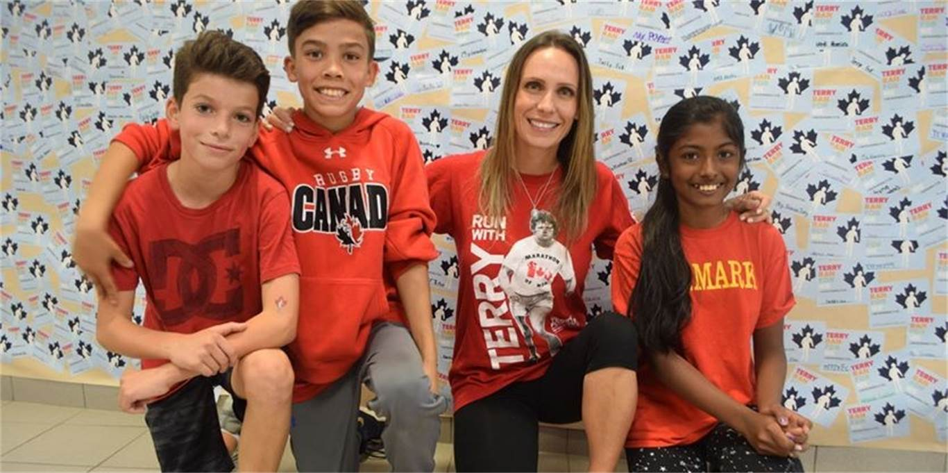 St. Mark Catholic Elementary School Grade 5 students Joseph Cino and Sean Butler, left to right, as well as Grade 6 student Michelle Bilan, far right, hang out with Lisa Poshni during the school's Terry Fox run/walk on Sept. 28. Poshni spoke about her experiences and life as a cancer survivor during an event kickoff assembly on Sept. 18. Photo by Laura Lennie.